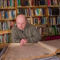 ymchwilydd-yn-chwilota-drwy-hen-bapur-newydd-a-researcher-searching-through-an-old-newspaper.jpg